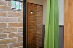脱衣スペースはカーテンで仕切られています。左手にバスルーム、レンガ柄のドアの先にトイレがあります。(2021-03-15,共用部,BATH,2F)