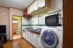キッチン脇に洗濯機が設置されています。洗濯機の上には電子レンジが置かれています。突き当たりが水まわり設備です。(2017-03-13,共用部,LAUNDRY,1F)