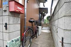 家の脇を進むと正面玄関があります。アプローチには共用の自転車が1台用意されています。(2019-08-22,共用部,GARAGE,1F)