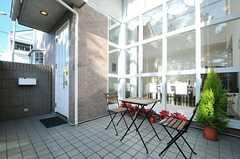 正面玄関の手前のテラスには、テーブルと椅子が置かれています。窓の奥にリビングが見えます。(2012-12-10,周辺環境,ENTRANCE,1F)