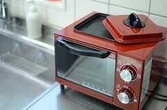 真っ赤なオーブントースターは、上部にプレートがはめ込まれており、パンを焼きながらその熱を利用して、同時に目玉焼きなども焼ける仕様。(2012-12-10,共用部,OTHER,1F)