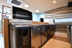 キッチンの対面は業務用の冷蔵庫が設置されています。冷蔵庫の上には電子レンジが2台置かれています。(2017-04-05,共用部,KITCHEN,1F)