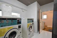 乾燥機が2台並んでいます。洗濯機は2階から上の各フロアに設置されています。奥がバスルームです。(2016-08-02,共用部,LAUNDRY,1F)