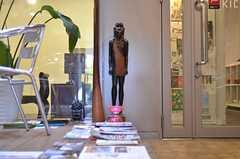 雑誌とフリーペーパーと木彫りの像。像の脇が多目的スペースの入口です。(2011-11-26,周辺環境,ENTRANCE,1F)