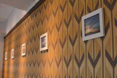 壁に飾られた写真は、入居者さんが近隣の海で撮影したものだそう。(2018-10-15,共用部,LIVINGROOM,1F)