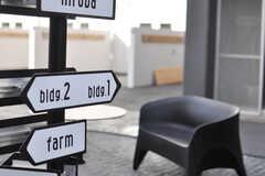 広場に立てられた矢印看板。カフェテーブルやベンチも置かれています。(2013-09-18,共用部,OTHER,1F)