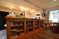 カウンターテーブルの下が大きな食器棚です。カウンターテーブルの上には、入居者さん持ち寄りの食品が置かれています。奥にキッチン家電が並んでいます。(2017-08-31,共用部,KITCHEN,1F)