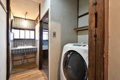 廊下に設置された洗濯乾燥機の様子。廊下の突き当りに洗面台があります。(2021-01-07,共用部,LAUNDRY,1F)