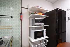 ガスコンロ脇に収納棚と冷蔵庫が並んでいます。収納棚にはキッチン家電が置かれています。(2016-10-25,共用部,KITCHEN,1F)