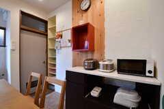 ダイニングテーブルの対面に収納棚が設置されています。収納棚には炊飯器や電子レンジが置かれています。(2017-05-15,共用部,KITCHEN,1F)