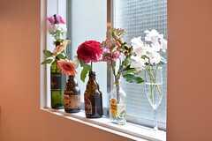 窓際には入居者さんが飾った花が並びます。(2016-02-16,共用部,LIVINGROOM,1F)