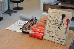 おみやげや差し入れのお菓子が置いてあることもあるそう。連絡事項はホワイトボードに書き込みができます。(2016-04-04,共用部,LIVINGROOM,2F)