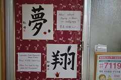 掲示板は包装紙。入居者向けのイベントも随時開催されています。署名の虹母とは運営事業者さんのこと。(2012-01-13,共用部,LIVINGROOM,1F)