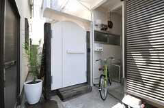 白いペンキで塗装された木製の門扉の様子。脇に設置された自転車は共用です。(2012-06-08,共用部,OUTLOOK,1F)
