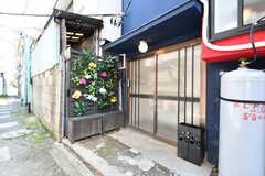 玄関の様子。玄関前には造花が飾られ、華やかです。傘立ても設置されています。(2019-05-23,周辺環境,ENTRANCE,1F)