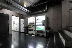 廊下の様子。左手ドアの奥にランドリーがあります。自動販売機脇からは宅配BOXへ続いています。(2011-08-26,共用部,OTHER,1F)