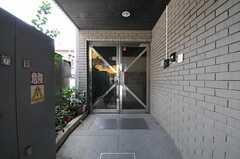マンションの正面玄関。ドアの左側にポスト、右側にインターホンがあります。(Machiya)(2011-08-12,周辺環境,ENTRANCE,1F)