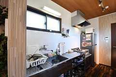 キッチンの様子。キッチンと冷蔵庫が並んでいます。冷蔵庫の上には電子レンジが置かれています。(2017-03-09,共用部,KITCHEN,1F)
