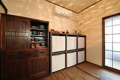 食器棚にはいろとりどりの食器類が並びます。脇の白い箱は部屋ごとに使える収納です。右手のガラス戸はバスルームです。(2014-04-28,共用部,KITCHEN,1F)
