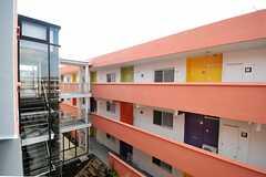 専有部の窓から見たB棟の様子。ドア周りのカラーは、イエロー、オレンジ、パープル、グリーンの4色です。(2012-03-14,共用部,OUTLOOK,3F)