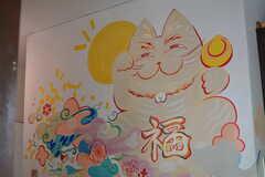 玄関で出迎えてくれる猫は、事業者さんの友人が描いたもの。猫だけでなく、室内の多くの壁にイラストが描かれています。(2021-06-08,周辺環境,ENTRANCE,1F)