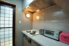 シンクの対面にあるガスコンロとキッチン家電の様子。(2012-08-31,共用部,KITCHEN,1F)