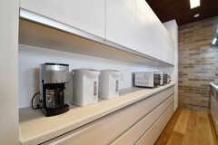 キッチンの対面は収納棚が設置されています。収納棚にはコーヒーメーカーや電子レンジが並んでいます。(2017-04-17,共用部,KITCHEN,1F)