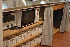 カーテンを開けると、キッチン家電や各部屋ごとに使用できる収納ボックスが。(2015-03-31,共用部,KITCHEN,1F)